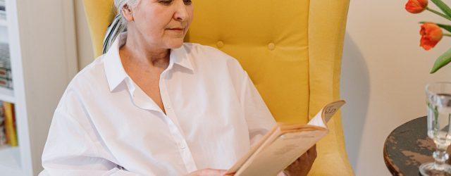 femme âgée en train de lire dans un fauteuil jaune