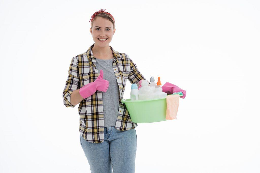 femme qui porte des gants de ménage et qui tient une bassine remplie de produits